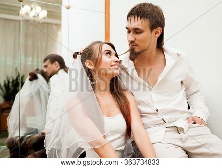Front View Of Happy Young Woman With Long Hair Sitting In Armchair With Fiance And Smiling. Adorable