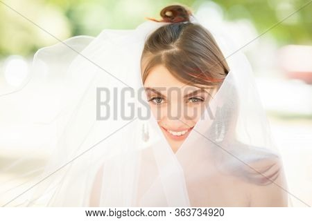Close Up Of Attractive Young Woman In Elegant Veil Looking At Camera And Smiling. Charming Newlywed