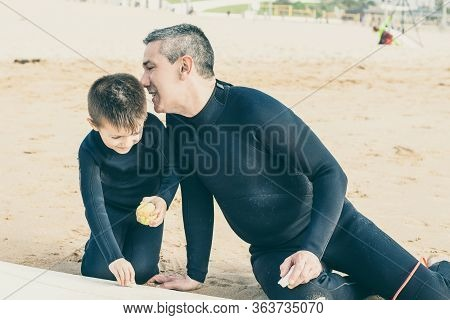 Father And Son Waxing Surfboard On Beach. Father And Little Son In Wetsuits Sitting On Sand And Waxi