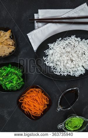 Rice With Korean Carrots, Soy Asparagus, Chuka, Wasabi, Soy Sauce And White Napkin On Black Backgrou
