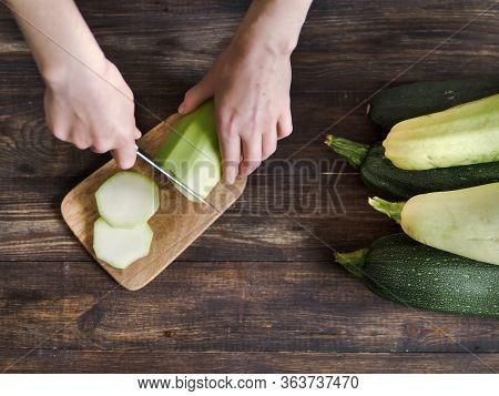 Zucchini Harvest. Woman Slices Zucchini On Wooden Table. Farm Organic Zucchini Harvesting