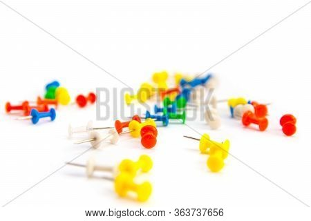 Multi-colored Pushpins Scattered Over A White-grey Background. Side View With Selective Focus