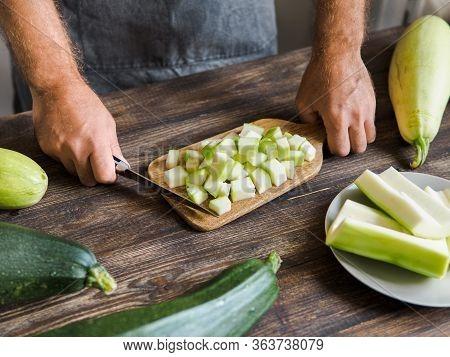 Zucchini Harvest. Man Slices Zucchini Cubes For Freezing On Wooden Table. Farm Organic Zucchini Harv