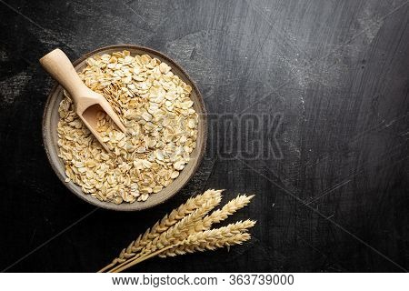 Rolled Oats Or Oat Flakes In Bowl And Wooden Spoon On Black Background, Top View With Copy Space