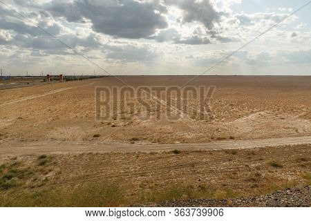 Steppe In Kazakhstan, Dry Grass In An Empty Steppe, Cloudy Sky