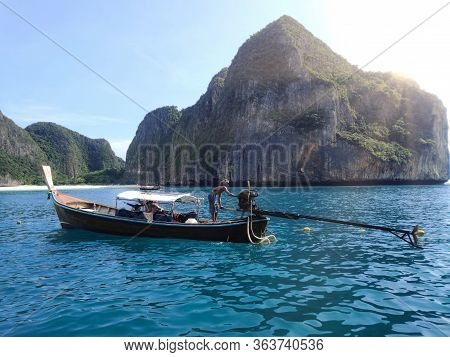 Long Tail On The Sea With Teal Water In Maya Bay In Phi-phi Thailand With Mountains On The Backgroun