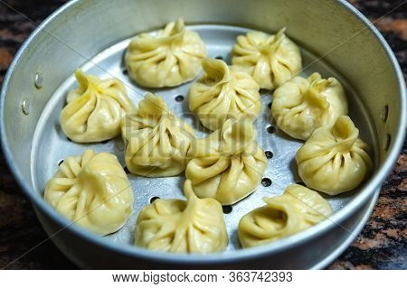 Home Made Traditional Dumpling Momos Food Of Nepal Served On The Momo Pot . Selective Focus