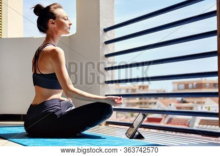 Girl Sit Cross-legged On Mat Do Meditation Practice At Home In Terrace Sunny Warm Day View. Use Tabl