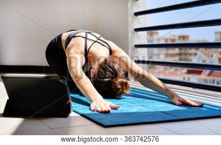 Woman Perform Yoga Child Pose On Mat Use On-line Session On Tablet. Workout At Home In Terrace Due T