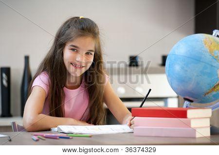 Smiling little girl doing her homework
