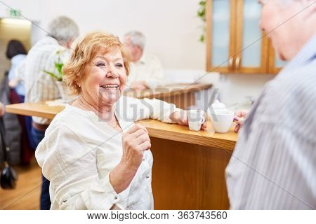 Cheerful elderly in the retirement home talks and flirts with senior in the common room