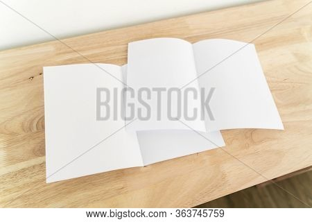 A4 half-fold brochure blank white template for mock up and presentation design on wooden surface.