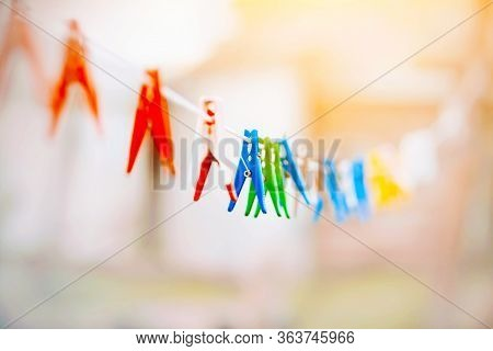 On A Bright Sunny Day, Colorful Bright Clothespins Hang On A Long White Clothesline, Waiting For Wet