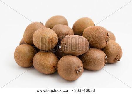 Pile Of Whole Brown Kiwi Fruits Isolated On White Background. Bunch Of Hairy Fresh Ripe Kiwifruits.