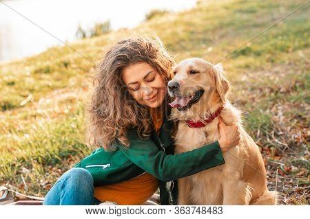 Smiling Woman Hugging Her Pet Golden Retriever Dog Near Face. Golden Retriever Dog Playing With A Cu