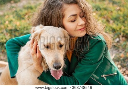 Curly Caucasian Woman Portrait Hugging Her Golden Retriever Dog In Summer Park. Green Color Backgrou