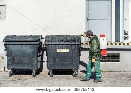 Ruzomberok, Slovakia - April 29, 2020: A Man In Protective Equipment Disinfects With A Sprayer In Th