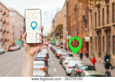 A Females Hand Holds A Smartphone With An Online Map App. In The Background Is A Blurred City Street