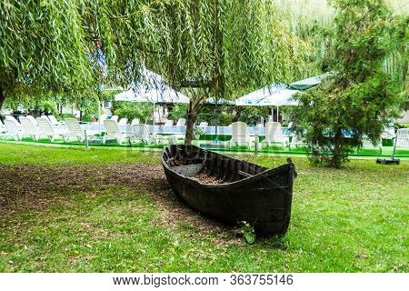 Uzlina, Delta Dunarii (danube Delta) - August 15, 2019: Old Wood Boat In A Garden Near The Pool And
