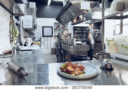 Behind The Scenes Of Brands. The Chef Cooking In A Professional Kitchen Of A Restaurant Meal For Cli
