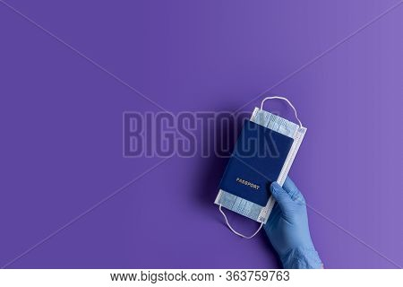 Doctor Holds Passports And Respiratory Surgical Face Mask In Hands Blue Medical Glove On Violet Back