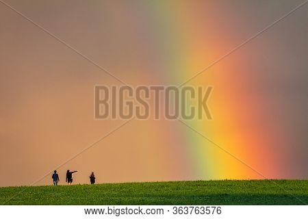Landscape Right After A Rain, Colorful Rainbow Over A Grassy Meadow With Young Peoples On A Walk.