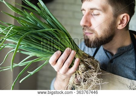 Young Man In Rustic Apron Holding And Smelling A Bunch Of Green Onions