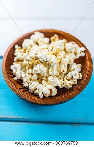 Popcorn In Wood Dish Or Bowl On Blue And White Table