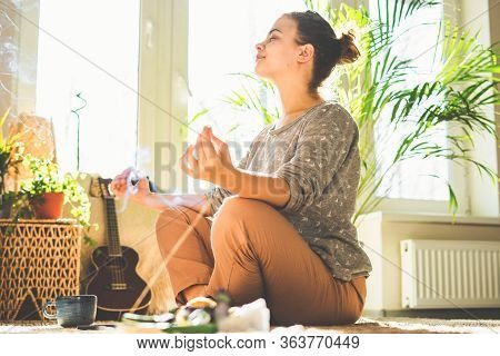 Beautiful Woman Doing Yoga, Meditates At Home In Sunny Day. Crystal And Aroma Stick Burn.