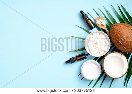 Flat Lay Composition With Coconut Oil Cosmetics And Tropical Palm Leaf On Blue Background. Top View
