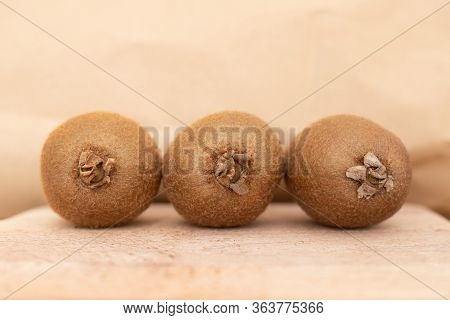 Whole Brown Kiwi Fruits Set On Wooden Table. Hairy Fresh Ripe Kiwifruits. Healthy Nutrition Or Organ