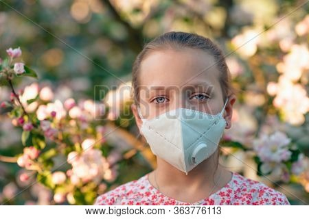 Young Girl In An Apple Orchard With Anti-smog Mask On The Face. Wearing Hygiene Masks Reduces The Ri