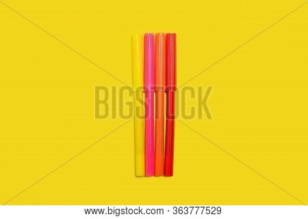 New Bright Plastic Multicolored Felt Pens Lying On A Yellow Background. Concept Of Office Supplies