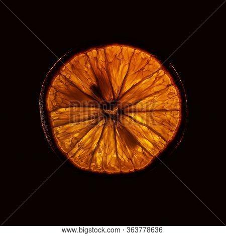 Slice Og Mature Orange Fruit With Backlight Isolated On Black Background