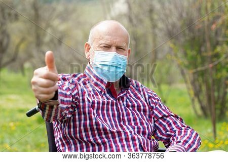 Elderly Man With Surgical Mask Sitting In A Wheel Chair Outdoor - Risk For Covid-19 Infection