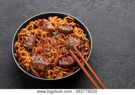 Ram-don Or Chapaguri Noodles With Beef Steak In Black Bowl On Dark Slate Background. Jjapaguri Is A