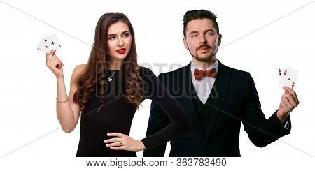 Woman In Black Dress And Man In Classic Suite Are Showing Two Aces. They Posing Isolated On White St