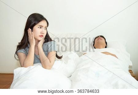 Asian Woman Getting Disturbed And Annoy With Man Sleep And Snoring On Bed. Bedroom, Authentic.