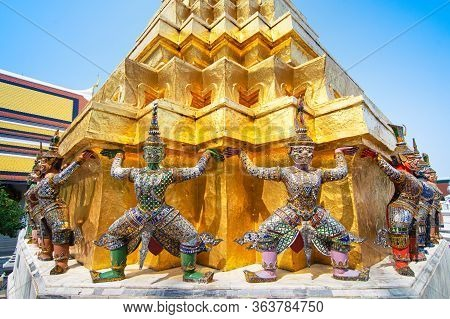 Golden Pagoda With Demon Guardian Yaksha At The Wat Phra Kaew Or The Temple Of The Emerald Buddha Wi