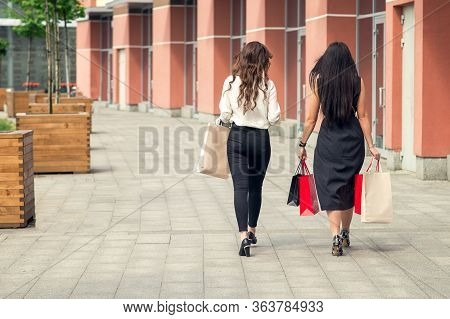 Back Side View Of Two Girls Walking Near Shopping Center Together Carrying Colorful Paperbags After