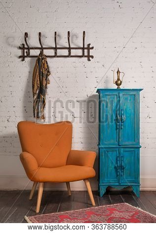 French Orange Wingback Armchair With Wooden Legs, Vintage Blue Cupboard, And Wall Hanger With Ornate