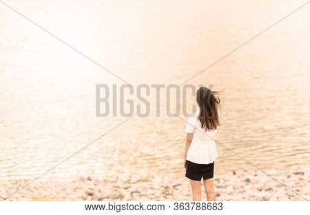 Young Woman Standing On Cliff And Looking Forward On The Background Of The Sea, Sky. Lady Tourist On