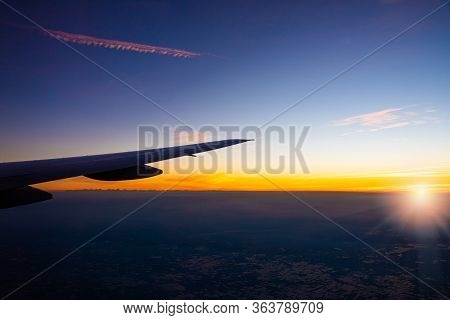 Sunset And Lens Flare In Twilight Time With Wing Of An Airplane And Cloud Sky. Photo Applied To Tour