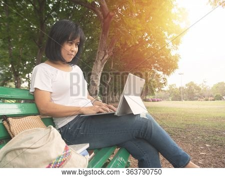 Asian Mid Adult Entrepreneur Businesswoman Sit In Park Using Laptop For Work Outside Office In Casua