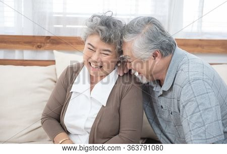 Romantic And Happy Asian Elder Senior Couple Laughing While Sitting On Sofa At Home