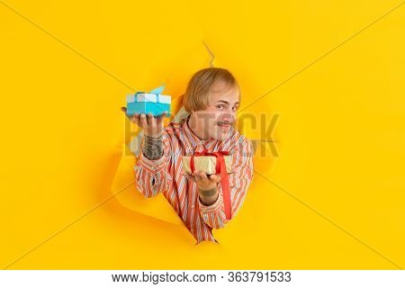 Gifts Giving. Cheerful Caucasian Young Man Poses In Torn Yellow Paper Background, Emotional And Expr