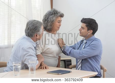 Caucasian Doctor Use Stethoscope And Talk With Old Asian Female Patient About Disease Symptom, Elder