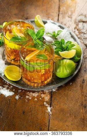 Refreshing Iced Drink With Lime, Mint And Rum Over Rustic Background With Copy Space. Top View. Refr