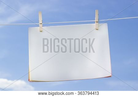 Blank Papers With Wooden Clothespins On Blue Sky. Paper Sheets Hanging On A Clothesline