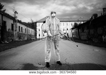Sanitation Worker In Hazmat Protection Suit  And N95 Mask With Chemical Decontamination Sprayer Tank